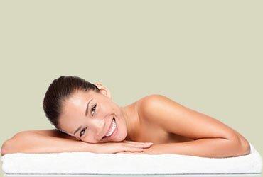 Ragazza sorridente che è distesa su lettino asciugamano al centro estetico Extetica pronta per massaggio estetista